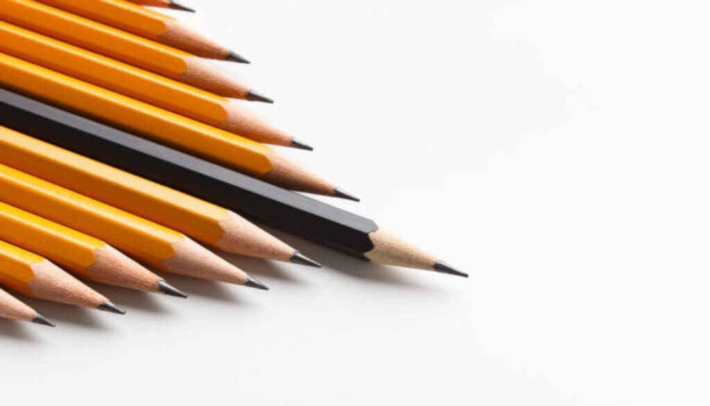 Group of yellow classic pencils following black one